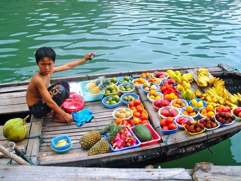 Young boy sells fruit on a boat in Vietnam
