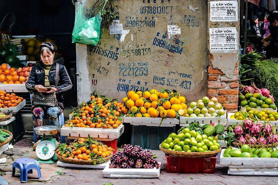 Fruit seller checks her phone on the streets of Vietnam