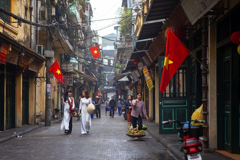 Two women in white dresses and fruit seller walk down traditional Vietnamese streets