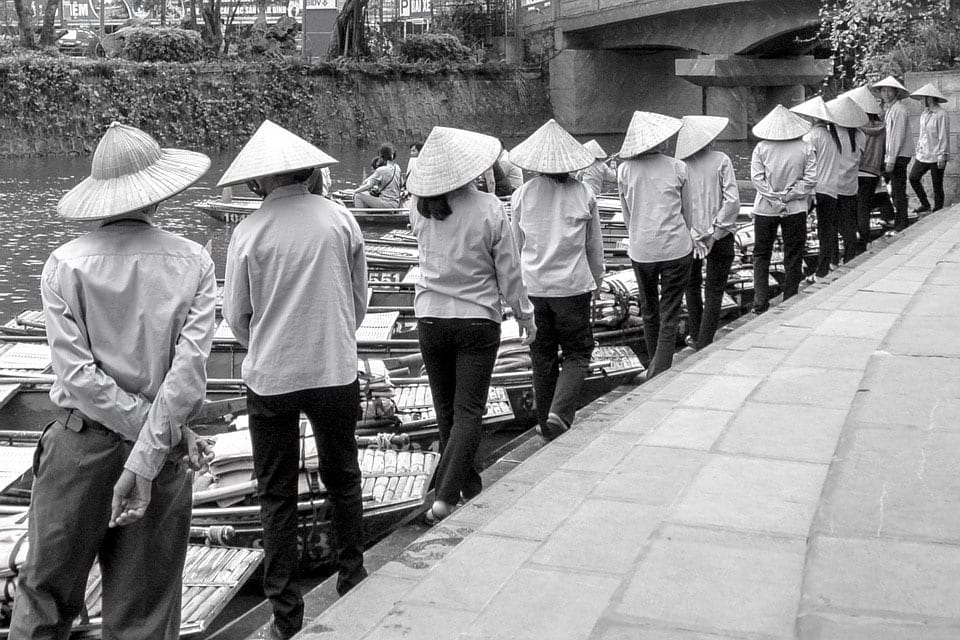 People in traditional Korean hats next to a river